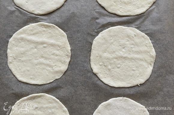 Затем каждый шарик раскатать в тонкую лепешку, переложить на противень, застеленный пергаментом. Накрыть противень пищевой пленкой и дать постоять еще 15–20 минут. В это время разогреть духовку до 260°C. Разогревать не менее 20 минут.