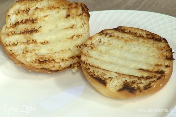 Булочки для бургера разрезать пополам, обжарить на сухой сковороде-гриль и смазать оставшимся соусом чили.