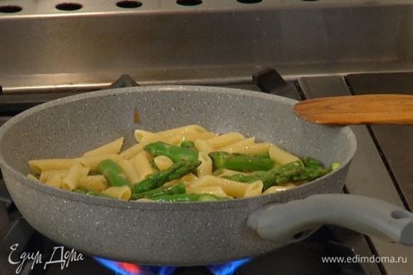Воду из макарон слить и сохранить, выложить пенне в сковороду со спаржей и прогревать все около минуты, доливая по необходимости оставленную воду, затем добавить сливочное масло и, помешивая, немного обжарить.