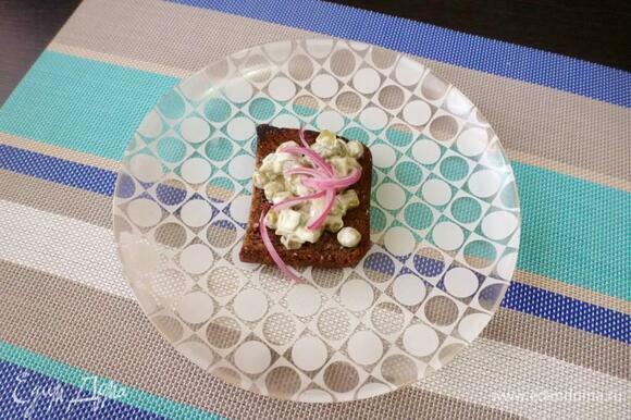 На кусочки поджаренного хлеба положить огуречный салат, а сверху — отжатый от уксуса лук.