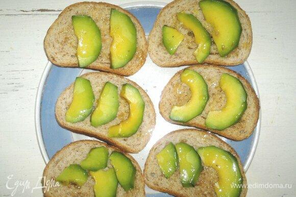 На хлеб выложить ломтики авокадо, полить льняным маслом.