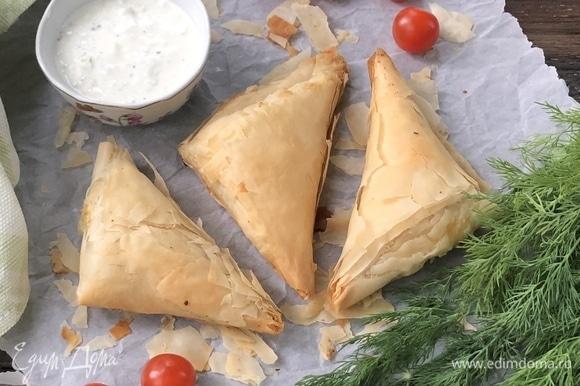 Для соуса один средний огурец натереть на крупной терке. Смешать с измельченной зеленью, сметаной и солью. Соус подавайте к пирожкам.