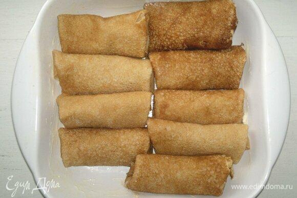Форму для запекания смазать сливочным маслом, выложить нафаршированные блинчики.