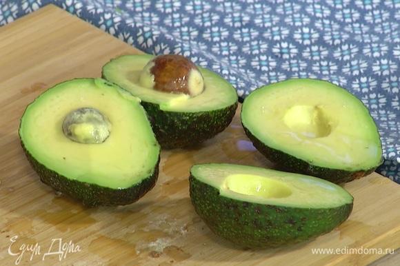 Авокадо разрезать пополам, удалить косточки, мякоть сбрызнуть лимонным соком.