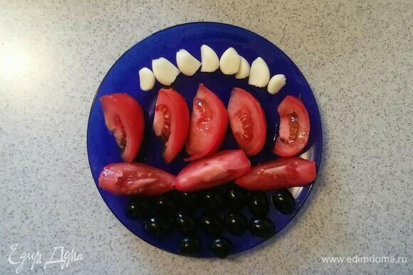 Зубчики чеснока и маслины нужно разрезать пополам, а помидор — на 8 равных частей.