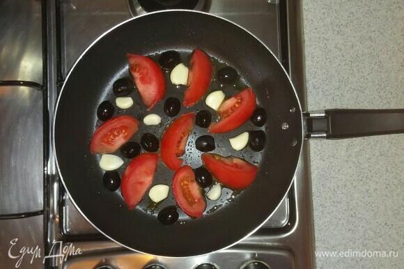 Смазываем сковороду маслом, выкладываем на нее овощи (половинки долек чеснока и маслины кладем стороной среза вниз) и ставим на мелкую конфорку плиты на средний огонь. Нужно обжарить овощи по 3–4 минуты с каждой стороны.