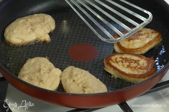Разогреть в тяжелой сковороде оливковое масло, ложкой выкладывать тесто и жарить оладьи с двух сторон.