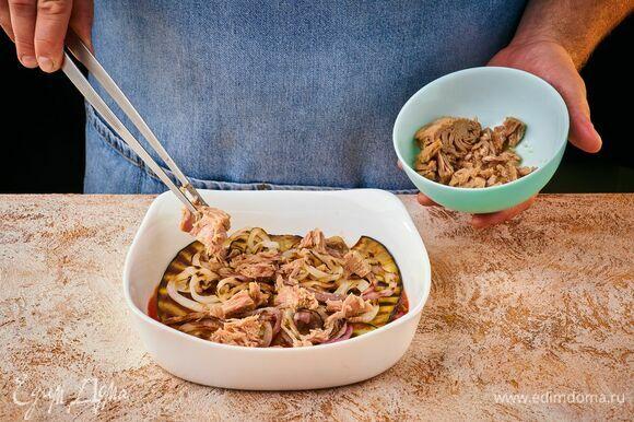 Выложите в форму часть готового соуса, затем — слой баклажана и лука. Далее — слой консервированного тунца.