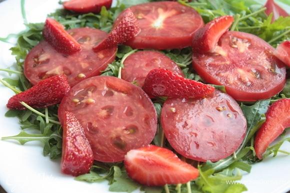 И начинайте собирать салат: сначала выкладываем заправленную руколу, поверх нее — помидоры, затем — клубнику и сыр. Завершающим штрихом будет бальзамический соус — им нужно слегка полить блюдо.