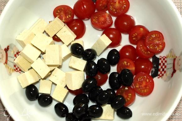 Все овощи хорошо промыть. В миску добавить помидоры черри, нарезанные половинками, тофу, нарезанный кубиками, маслины.