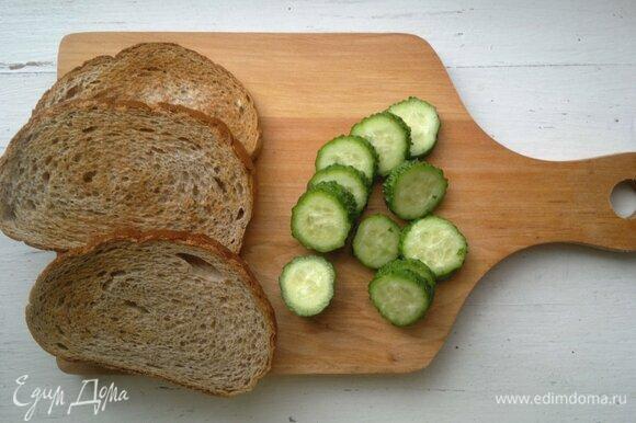 Ломтики батона поджарить в тостере или на сухой сковороде. Огурец вымыть, обсушить, нарезать тонкими кружками.