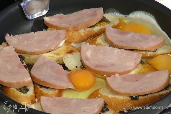 Ветчину нарезать тонкими ломтиками, выложить сверху на хлеб, разбить в сковороду яйца, посолить и поперчить, накрыть крышкой и жарить до готовности яиц.