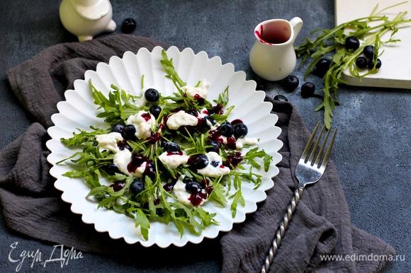 Выложите листья руколы в салатницу, добавьте чернику и сыр. Полейте салат ягодным соусом.