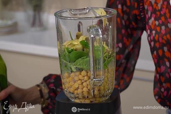 Готовый нут, шпинат, артишоки и чеснок выложить в чашу блендера, добавить пасту тахини, оливковое масло и сок лимона, все посолить и взбить в однородную, гладкую массу.