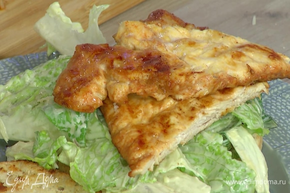 На нижнюю часть булочки выложить салат, обжаренную отбивную и помидор, накрыть второй половиной булочки.