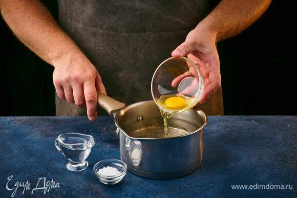 Сварите яйцо пашот. Сотейник наполните водой, добавьте уксус и соль, перемешайте. Яйцо заранее аккуратно разбейте в маленькую миску. Воду доведите до кипения, сделайте средний огонь. При помощи венчика закрутите воронку и быстро, но осторожно опустите яйцо в центр этой воронки. Варите 2 минуты.