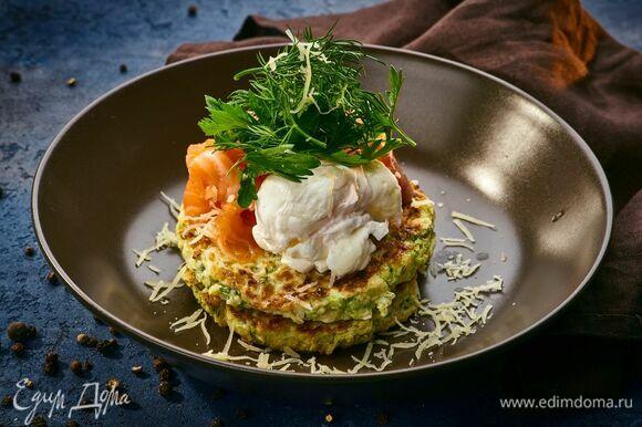 Подавайте оладьи из кабачков, посыпав тертым сыром. Сверху выложите яйцо пашот и кусочки свежесоленого лосося. По желанию добавьте сметану.