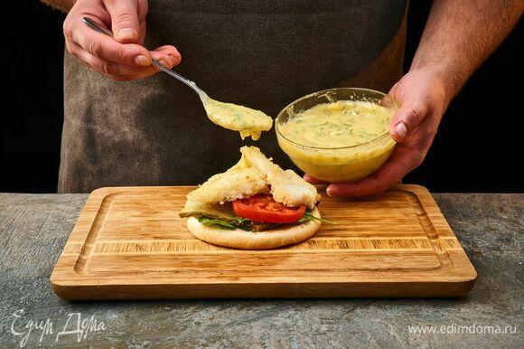 Нижнюю половину булочки полейте соусом, выложите листья шпината, сверху — помидоры, лук и соленые огурцы, далее — обжаренную рыбу и соус.