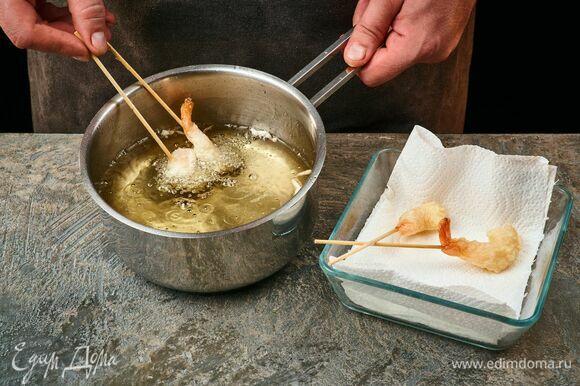 Доведите до кипения растительное масло в сковороде или сотейнике. Опустите креветки в кляре в масло. Обжаривайте со всех сторон до румяной корочки около минуты. Готовые жареные креветки выложите на бумажное полотенце, чтобы удалить остатки масла.