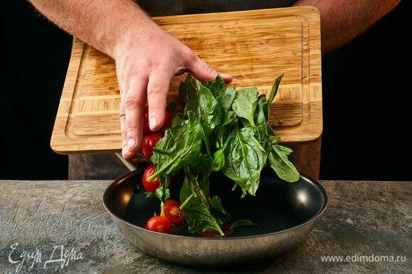 Обжарьте шпинат в оливковом масле с измельченным зубчиком чеснока. Добавьте помидоры черри, разрезанные пополам, посолите и поперчите.