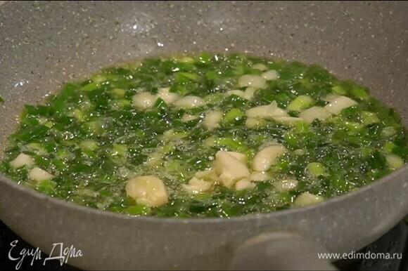 Разогреть в сковороде сливочное и оливковое масло, выложить лук с чесноком, слегка посолить и обжарить.