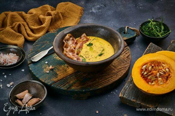 Разлейте суп по тарелкам, выложите сверху бекон, украсьте зеленью.