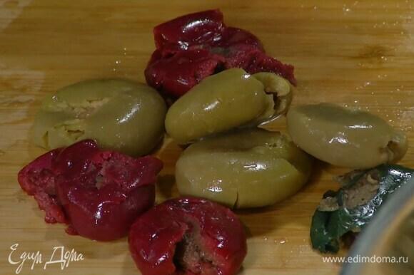 Оливки раздавить дном стакана и, вынув косточки, разломить на крупные кусочки.